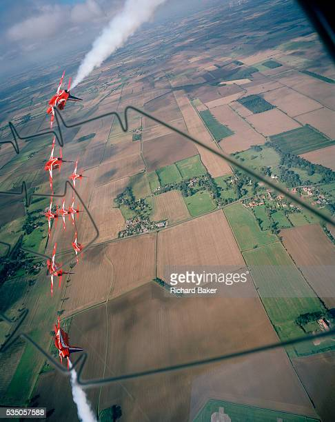 Banking hard right over the agricultural Lincolnshire countryside are the elite 'Red Arrows' Britain's prestigious Royal Air Force aerobatic team who...