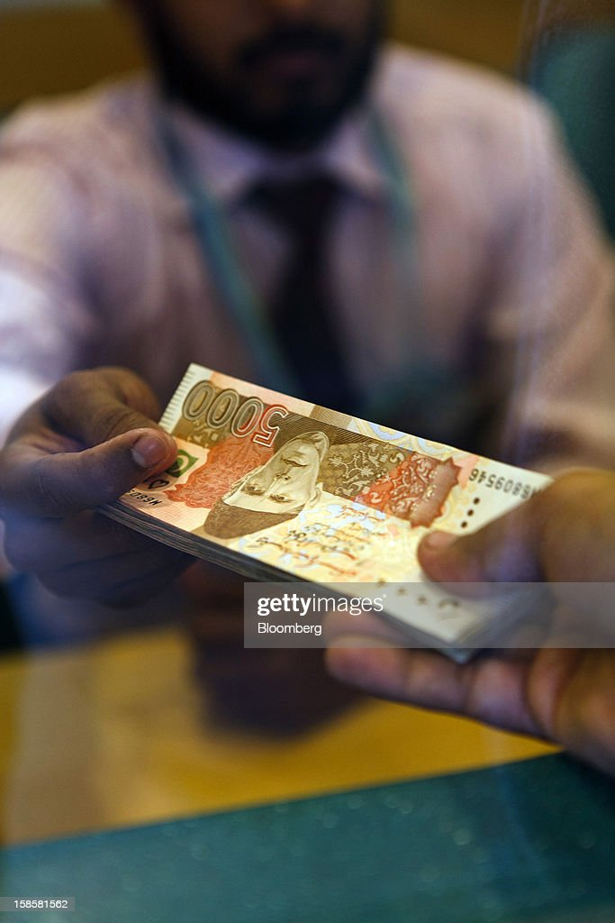 A BankIslami Pakistan Ltd. bank teller holds a stack of bank notes at a counter in one of the bank's branches in Karachi, Pakistan, on Tuesday, Dec. 18, 2012. BankIslami, the nation's second-biggest Islamic bank, is targeting a 50 percent profit increase next year as it doubles its branches to meet demand for Shariah-compliant services. Photographer: Asim Hafeez/Bloomberg via Getty Images