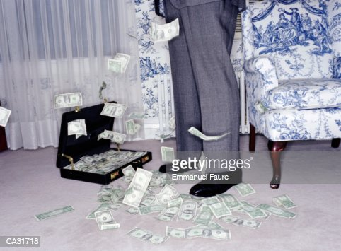 US banknotes falling around man in hotel room, low section : Stock Photo