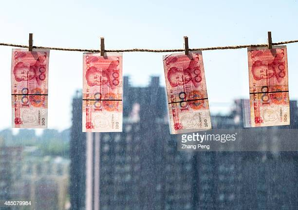 RMB banknotes hanging in front of window arranged for photograph China's recent devaluation of the RMB has created waves in domestic and global...