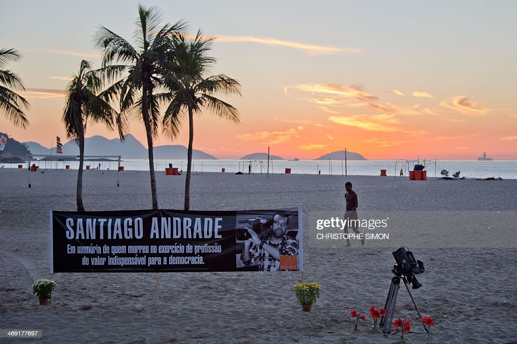 A banner and a camera are seen on the beach of Copacabana, on February 13, 2014 in Rio de Janeiro, Brazil, in homage to Brazilian cameraman Santiago Andrade, who died after being hit in the head with some kind of explosive device during clashes between demonstrators protesting against a hike on bus fares and riot police in Rio de Janeiro on February 6. AFP PHOTO / CHRISTOPHE SIMON