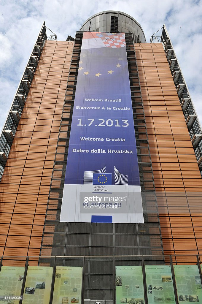 A banner announcing the arrival of Croatia into the EU is seen hanging on a main wall of the Berlaymont building at the EU Headquarters in Brussels on June 25, 2013. From July 1, 2013, Croatia will be the 28th country to enter in the European Community. The first new member of the club since Bulgaria and Romania joined in 2007 is proving unpopular in the streets, where opinion polls show a majority of Europeans have turned against enlargement after years of grinding recession and austerity. AFP PHOTO/GEORGES GOBET