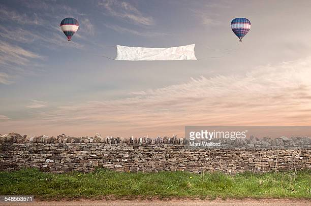 Banner between two hot air balloons over a Cotswold stone wall