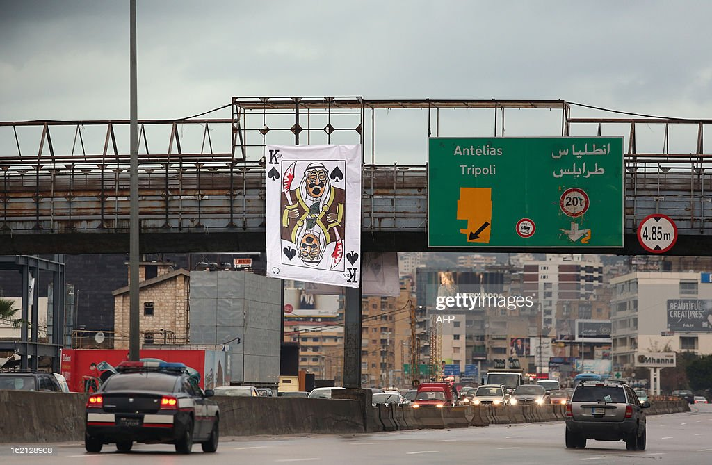 A banner depicting Saudi Arabia's King Abdullah bin Abdul Aziz as the King of Spades holding a blood-stained sword hangs on a bridge north of the Lebanese capital Beirut on February 19, 2013.