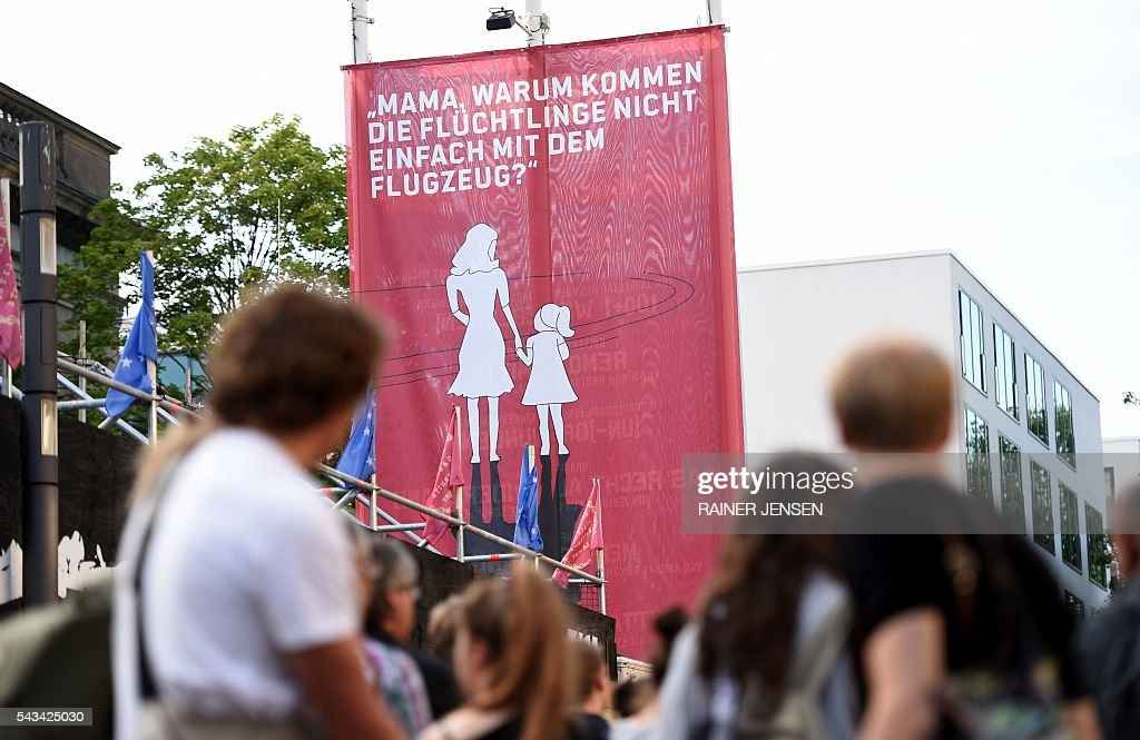 A banner featuring a child asking her mother 'Mama, why do the refugees not simply come by airplane?' as people gather in front of the Gorki-Theater in Berlin on June 28, 2016 after the plans by German activists of the so-called 'Center for Political Beauty' were cancelled to fly in 100 refugees to Berlin-Tegel airport in a chartered airplane. / AFP / dpa / Rainer Jensen / Germany OUT