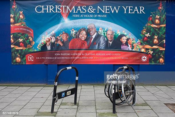 A banner for the black church House of Praise with abandoned and locked bicycle wheels in Walworth south London Church members and officials stare...