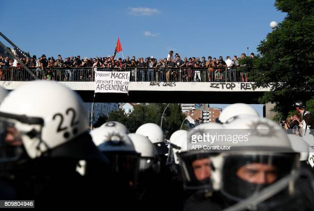 A banner hangs from a bridge which reads 'President Macri Dont sell our Argentina' as riot police escort the 'Welcome to Hell' rally against the G20...