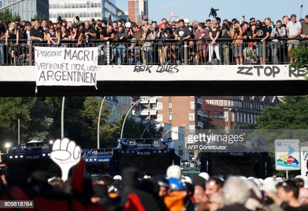A banner hangs from a bridge which reads 'President Macri Dont sell our Argentina' as riot police with water cannon block the 'Welcome to Hell' rally...