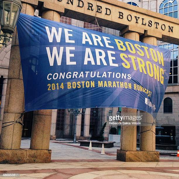 A banner honoring the 2014 Boston Marathon is strung from pillars on Boylston Street and strains in a strong wind