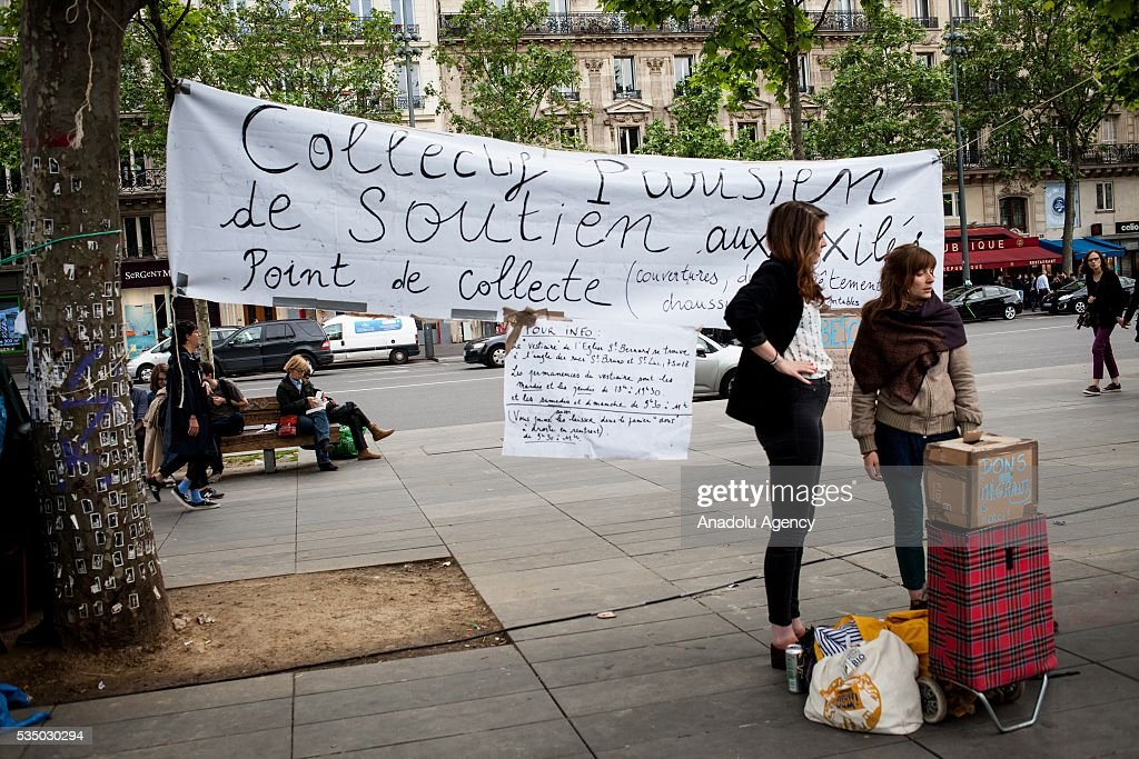 Banner of the Commission for refugees at 'Nuit Debout' global meeting Place de la Republique in Paris, France on May 28, 2016.