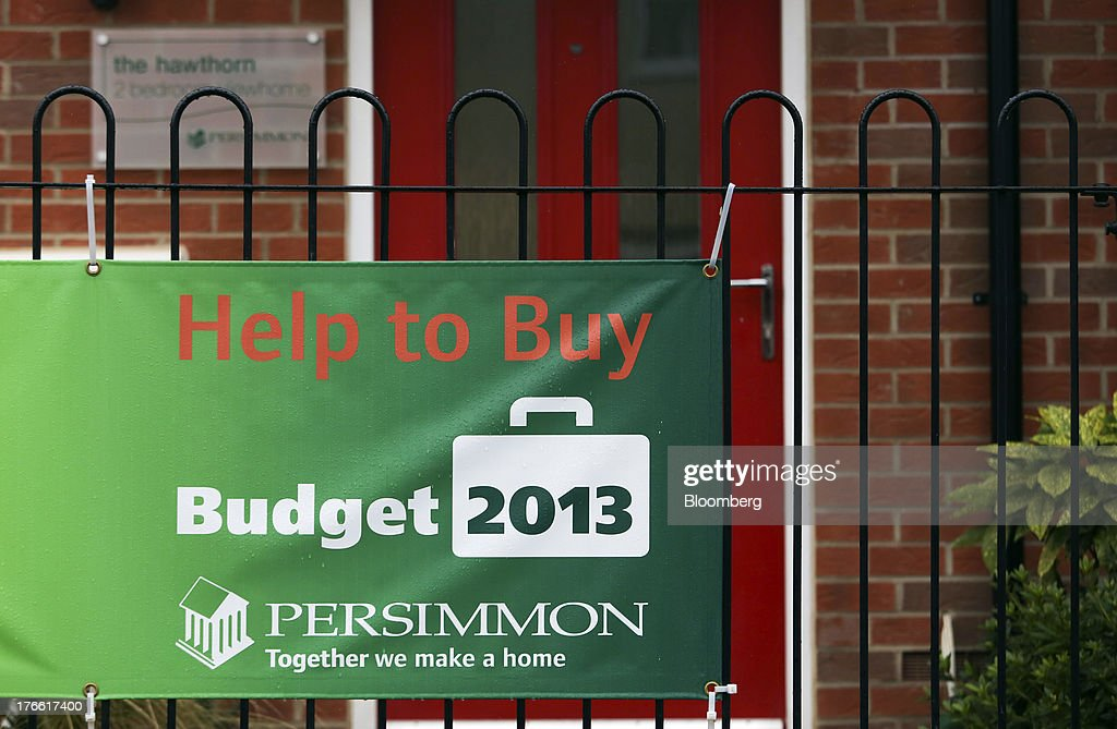 A banner promoting the U.K. government's 'Help to Buy' housing initiative sits on railings outside a newly constructed house at a Persimmon Plc residential building site in Romford, U.K., on Friday, Aug. 16, 2013. Persimmon, the largest homebuilder by market value, said in July that its operating margin widened to about 15 percent during the half from 12.1 percent. Photographer: Chris Ratcliffe/Bloomberg via Getty Images