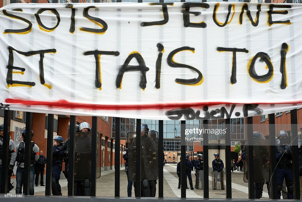 A banner reading 'be young and shut up !' hanged on the metal gate of the General Council of Haute-Garonne during a protest against the El-Khomri bill on labour reforms. Riot police stand inside. Toulouse. France. May 3th 2016.