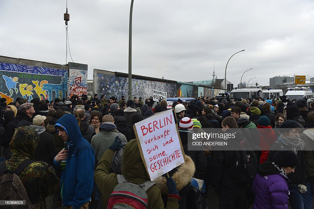 A banner reading 'Berlin sells itself and its history' during a protestors against the removal of a section of the East Side Gallery, a 1,3 km long remainder of the Berlin Wall, for a housing construction project near the city's east railway station in Berlin on March 1, 2013. Some 25 meters of this section of the wall that mostly came down 23 years ago and marked the end of the cold war are taken away to make way for a new housing development on river Spree, a project called Living Levels. As news of this spread activists and artists that had decorated this remaining part of the cold war relic known as the east side gallery came to protest. AFP PHOTO / ODD ANDERSEN