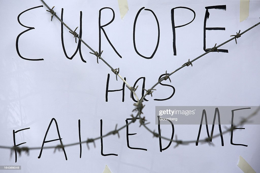 A banner reading 'Europe has failed me' hangs from fencing behind barbed wire outside the Cypriot parliament in Nicosia, Cyprus, on Saturday, March 23, 2013. The aid package Cyprus is seeking would only provide temporary relief as it risks triggering a capital flight that would push the nation closer to needing to restructure its debts. Photographer: Simon Dawson/Bloomberg via Getty Images