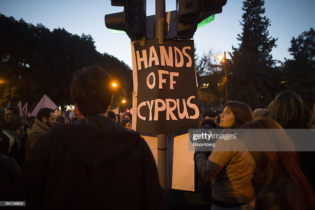 A banner reading 'Hands off Cyprus' hangs from a traffic signal during a demonstration outside the parliament against bank deposit tax plans in Nicosia, Cyprus, on Tuesday, March 19, 2013. Euro-area finance ministers told Cyprus to raise 5.8 billion euros ($7.5 billion) from bank depositors to unlock emergency loans, maintaining the revenue target while suggesting sparing small-scale savers. Photographer: Simon Dawson/Bloomberg via Getty Images