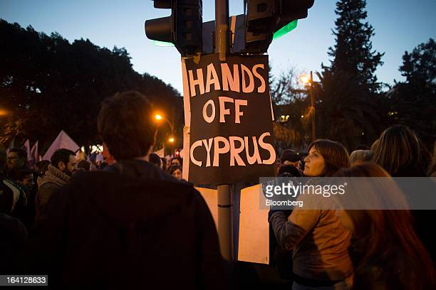 A banner reading 'Hands off Cyprus' hangs from a traffic signal during a demonstration outside the parliament against bank deposit tax plans in...