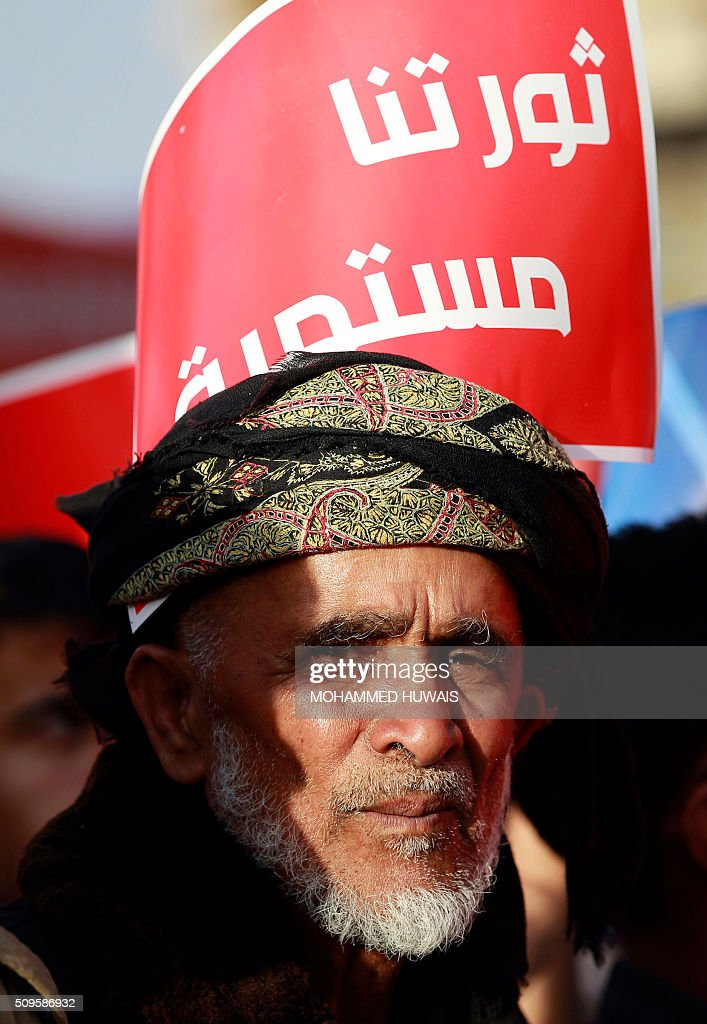 'our revolution continues' is seen behind a supporter of the Shiite Huthi movement during a rally commemorating the fifth anniversary of the 2011 Arab Spring uprising that toppled the then-president Ali Abdullah Saleh, on February 11, 2016 in the capital Sanaa. / AFP / MOHAMMED HUWAIS