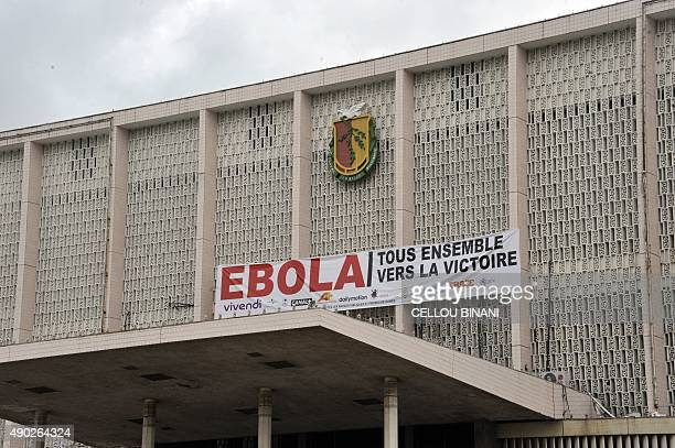 A banner reading in French 'Ebola All together for victory' is hang to a building during a concert gathering artists from across Africa to celebrate...
