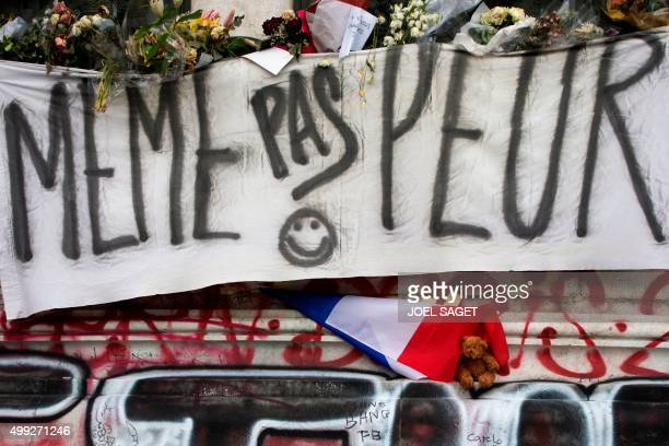 A banner reading 'Not afraid' is pictured next to a French flag and a teddy bear at a makeshift memorial for the victims ot November 13 terrorist...