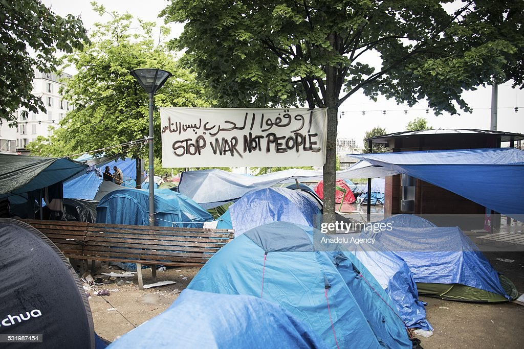 A banner, reading 'Stop War Not People' is seen as refugees live in harsh conditions at a makeshift camp set at the Jardin d'Eole in Paris on May 28, 2016.