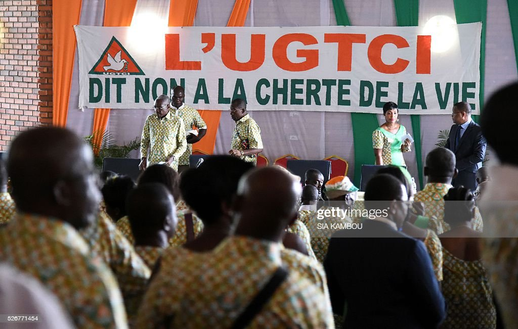 A banner reading 'The UGTCI says no to the high cost of living' is displayed at the Bourse du Travail in Abidjan on May 1, 2016 during an International Worders' Day celebration held by the 'Union Generale des Travailleurs de Cote d'Ivoire' union. / AFP / SIA