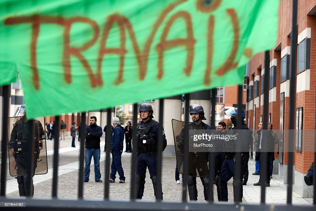 A banner reading Work' hanged on the metal gate of the General Council of Haute-Garonne during a protest against the El-Khomri bill on labour reforms. Riot police stand inside. Toulouse. France. May 3th 2016.