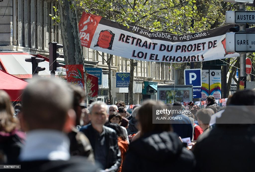 A banner reads 'Neither amendable nor negotiable - the withdrawal of the El Khomri laour law bill' as people take part in the traditional May Day demonstration in Paris on May 1, 2016.
