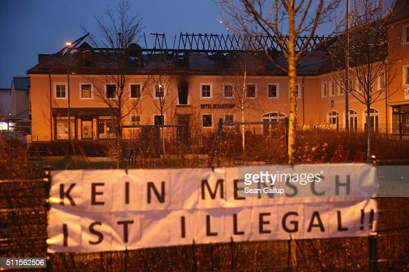 A banner reads 'No person is illegal' which is a slogan common among activists advocating refugee rights in Germany next to the burntout remains of a...