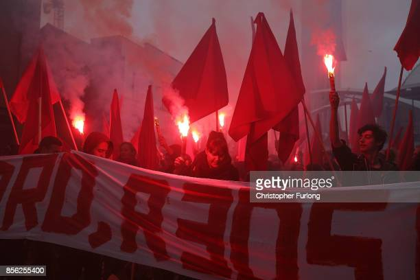 A banner saying 'Forward Reds' is held up along with red flares as people take part in antiBrexit and antiausterity protests as the Conservative...