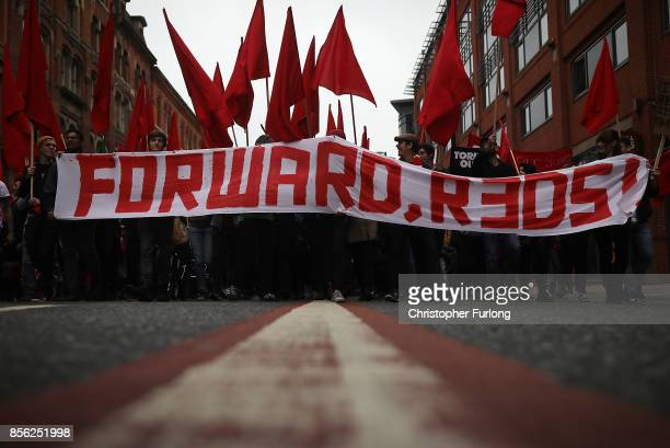 A banner saying 'Forward Reds' is held up as people take part in antiBrexit and antiausterity protests as the Conservative party annual conference...
