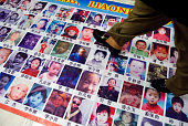 A banner showing the images of children that have gone missing in China since the 1980s sits on the floor outside of a House Foreign Affairs...