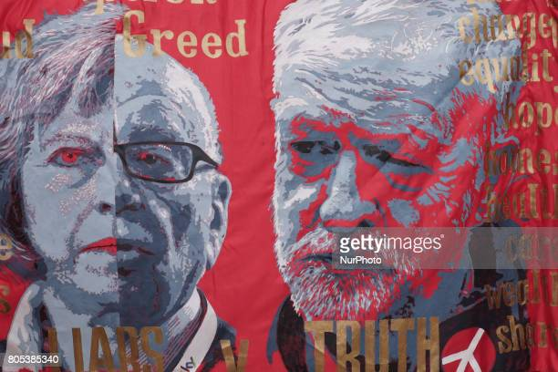 A banner shows a Jeremy Corbyn and Theresa May with Rupert Merdoch having the same face in London United Kingdom on July 1 2017 Tens of thousands of...