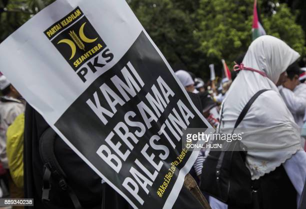 A banner that reads 'We are with Palestinians' is displayed as demonstrators attend a protest against US President Donald Trump's recognition of...