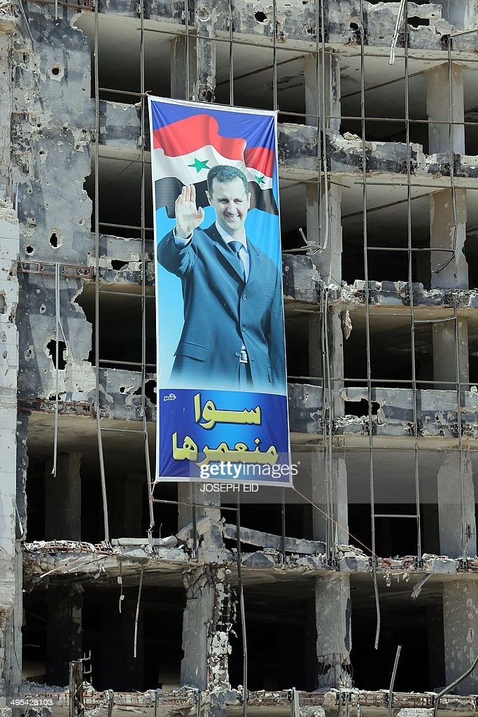 A banner with a picture of Syrian President Bashar Assad with a slogan reading in Arabic ' we build it together' hangs on a destroyed building in the...