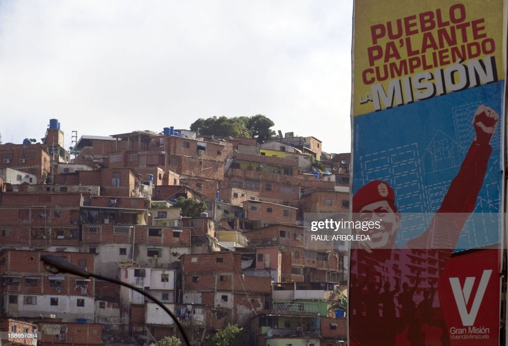 A banner with the image of Venezuelan President Hugo Chavez is seen in the streets of the populous Petare slum in Caracas on January 4, 2013. Hugo Chavez's top aides have gone on the offensive, accusing the opposition and media of waging a 'psychological war,' as Venezuela's cancer-stricken president battles a serious lung infection. The closing of ranks followed a high-level gathering of top Venezuelan officials in Havana with Chavez, amid growing demands to know whether he will be fit on January 10 to take the oath of office for another six-year-term. AFP PHOTO/Raul ARBOLEDA