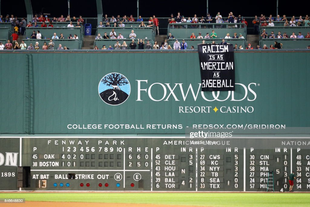 A banner with the message 'Racism is as American as baseball' is draped over the Green Monster during the fourth inning of the game between the Boston Red Sox and the Oakland Athletics at Fenway Park on September 13, 2017 in Boston, Massachusetts.