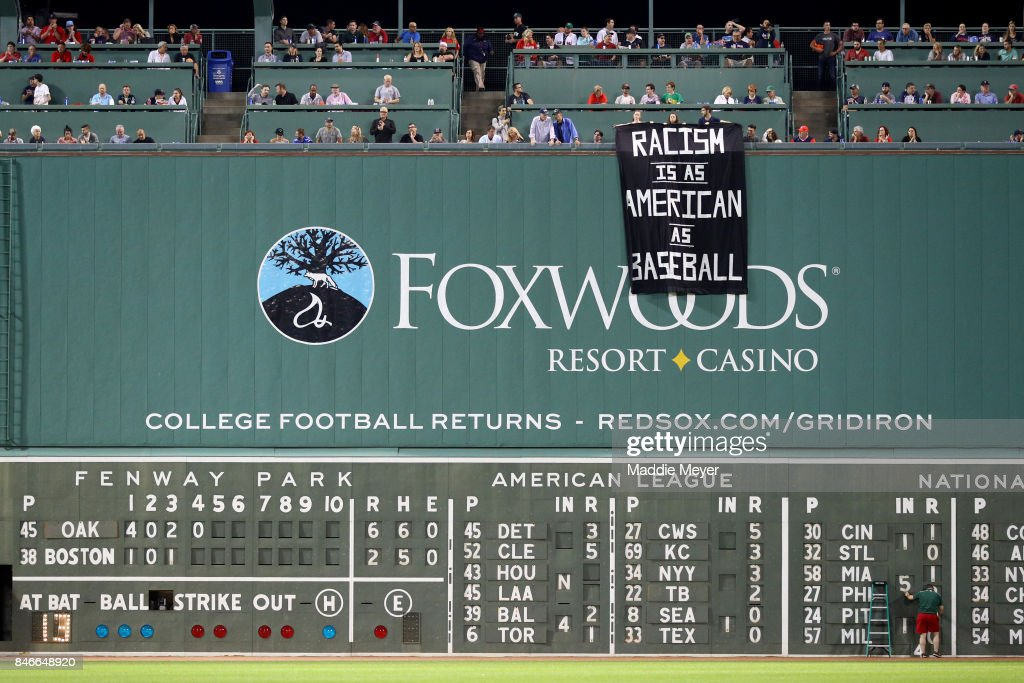 A banner with the message 'Racism is as American as baseball' is draped over the Green Monster by fans during the fourth inning of the game between the Boston Red Sox and the Oakland Athletics at Fenway Park on September 13, 2017 in Boston, Massachusetts.