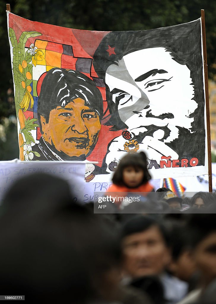 A banner with the portraits of Bolivian President Evo Morales adn Argentine-born revolutionary leader Ernesto 'Che' Guevara is seen during a celebration for the reincorporation of Bolivia to the UN Convention Against Illicit Traffic in Narcotic Drugs in La Paz on January 14, 2013. 'The coca leaf is not any more seen as cocaine (..), it is a victory of our identity' said Morales. AFP PHOTO/Jorge Bernal