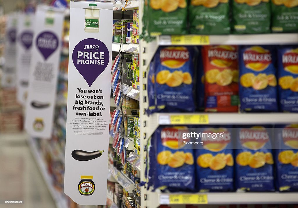 Banners alert customers to Tesco's new 'Price Promise' initiative inside a Tesco Plc supermarket in the borough of Kensington in London, U.K., on Tuesday, March 12, 2013. Tesco Plc, the U.K.'s largest grocer launched a 'Price Promise', its latest initiative offering to match the price of customers' purchases to that of it's rivals, including Wal-Mart Stores Inc.'s ASDA. Photographer: Simon Dawson/Bloomberg via Getty Images