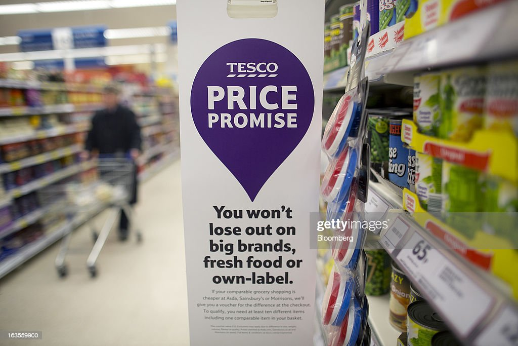 A banners alerts customers to Tesco's new 'Price Promise' initiative inside a Tesco Plc supermarket in the borough of Kensington in London, U.K., on Tuesday, March 12, 2013. Tesco Plc, the U.K.'s largest grocer launched a 'Price Promise', its latest initiative offering to match the price of customers' purchases to that of it's rivals, including Wal-Mart Stores Inc.'s ASDA. Photographer: Simon Dawson/Bloomberg via Getty Images