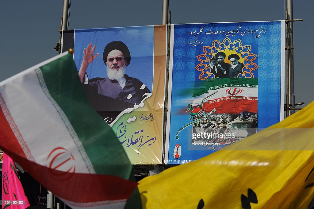 Banners and Iranian flag go past large posters of <a gi-track='captionPersonalityLinkClicked' href=/galleries/search?phrase=Ayatollah+Khomeini&family=editorial&specificpeople=226737 ng-click='$event.stopPropagation()'>Ayatollah Khomeini</a> depicting his return from France, during the 34th anniversary of the Islamic revolution in Azadi square on February 10, 2013 in Tehran, Iran.