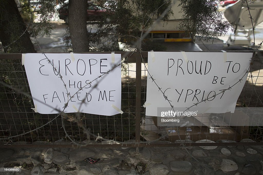 Banners reading 'Europe has failed me' and 'Proud to be Cypriot' hang from fencing behind barbed wire outside the Cypriot parliament in Nicosia, Cyprus, on Saturday, March 23, 2013. The aid package Cyprus is seeking would only provide temporary relief as it risks triggering a capital flight that would push the nation closer to needing to restructure its debts. Photographer: Simon Dawson/Bloomberg via Getty Images