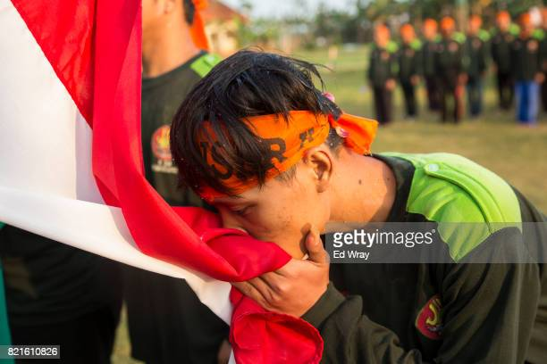Banser recruit kisses the Indonesian flag at the graduation ceremony after a rigorous three day induction course on July 23 2017 in Kebumen Indonesia...