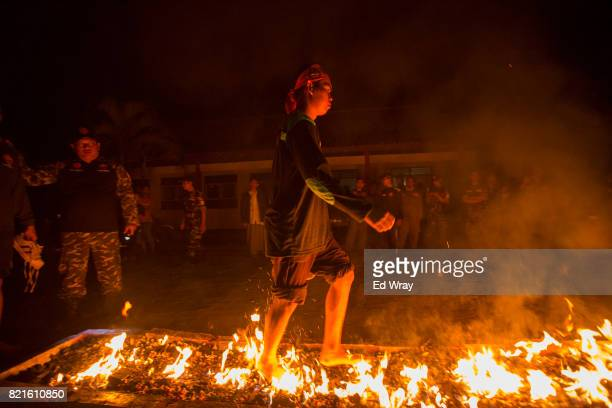 Banser recruit walks over burning coals as part of an initiation during a rigorous three day induction course on July 22 2017 in Kebumen Indonesia...