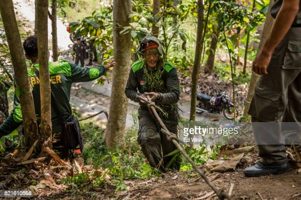 Banser recruit wearing camouflage climbs up a steep hill using a rope during a rigorous three day induction course on July 23 2017 in Kebumen...