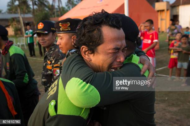 A Banser recruit weeps as he hugs an instructor at a graduation ceremony after a rigorous three day induction course on July 23 2017 in Kebumen...