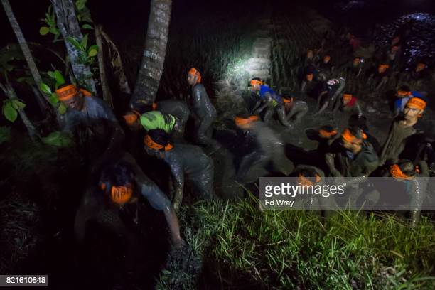 Banser recruits emerge from a muddy rice paddy during a 3 am run through an obstacle course during a rigorous three day induction course on July 22...