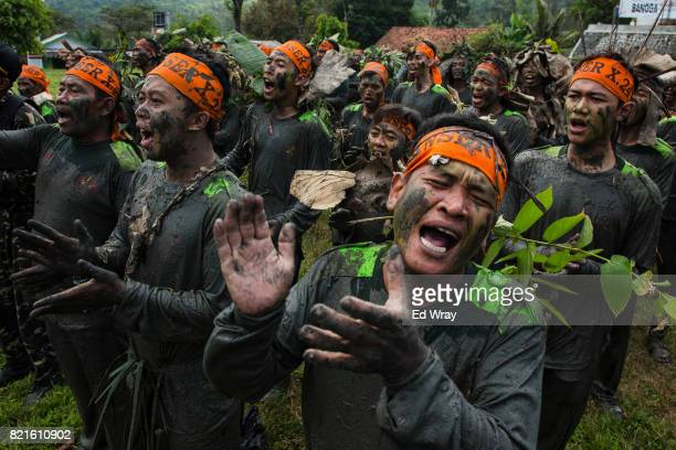 Banser recruits wearing camouflage sing the Banser song before the start of the penultimate 5 hour run though an obstacle course during a rigorous...