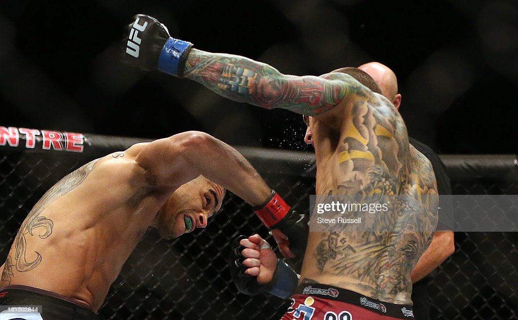 TORONTO, ON- SEPTEMBER 21 - Bantamweight Renan Barão from Brazil punches, he would retain his interim title with a knock out via spinning back kick to Eddie Wineland from Indiana at UFC 165 at the Air Canada Centre in Toronto, September 21, 2013.