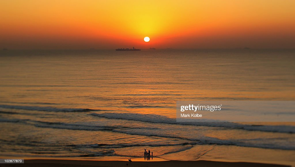 A baptism is performed as the sunrises over the Indian Ocean on June 19, 2010 in Durban, South Africa.